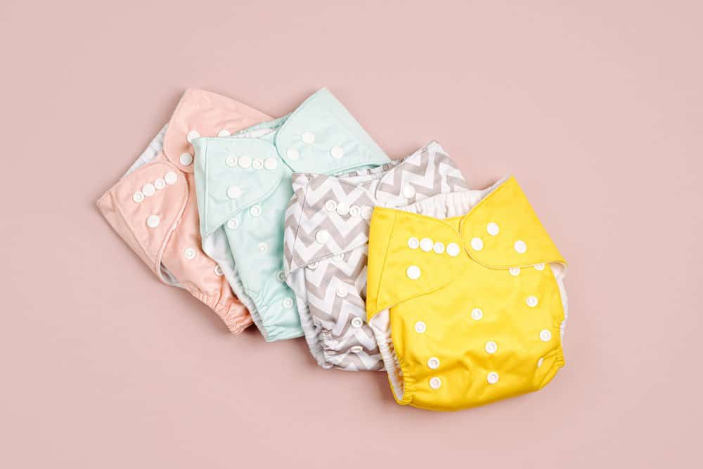 Reusable cloth baby diapers. Eco friendly cloth nappies on a pink background. Sustainable lifestyle. Zero waste concept.