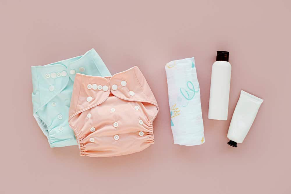 Set of cloth diaper and baby cosmetics. Eco friendly cloth nappies for newborn. Baby hygiene concept. Flat lay, top view