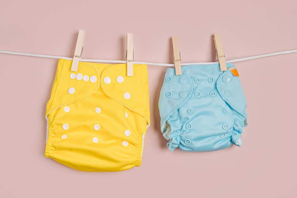 Reusable cloth baby diapers drying on a clothes line. Eco friendly cloth nappies on a pink background. Sustainable lifestyle. Zero waste concept.